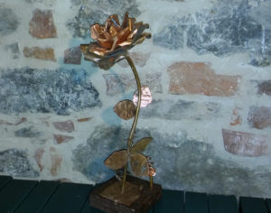 natural and ageed copper coloured rose on handmade wooden base